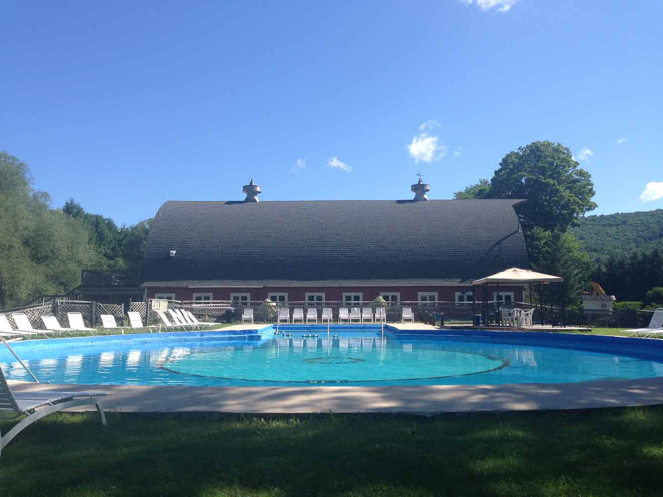 large round built in pool with chaise lounges and barn in background at Homestead Farm Resort Margaretville NY
